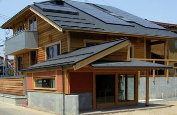 ログハウス風の木の外壁とソーラーパネル.png